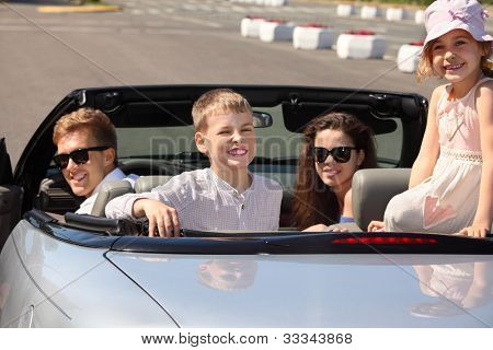 Happy father, mother and two children sit in convertible car and look back; focus on children