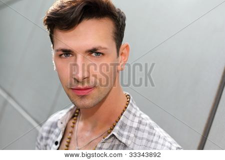 Young beautiful man stands near gray wall and looks at camera