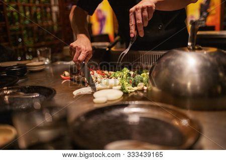 Teppanyaki Chef Preparing Japanese Cuisine On Hot Metal Plate By Cutting Up Vegetables