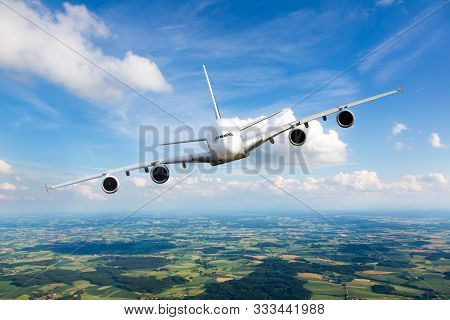 White Passenger Plane In Flight. The Plane Flies Against A Background Of A Endless Horizon. Aircraft