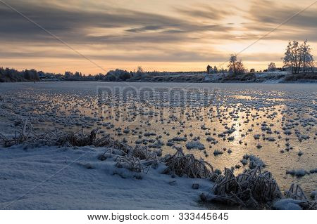 The Winter Sun Rises Over The Freezing River At The Northern Finland. The River Surface Is Covered W