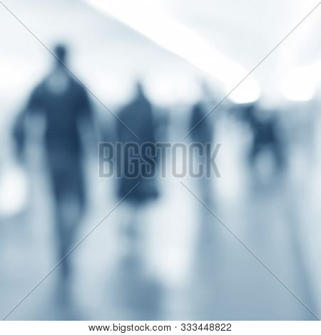 People Walking In An Underground Passage. Silhouettes Of Passengers In Blur. Blurred Image Of Moving