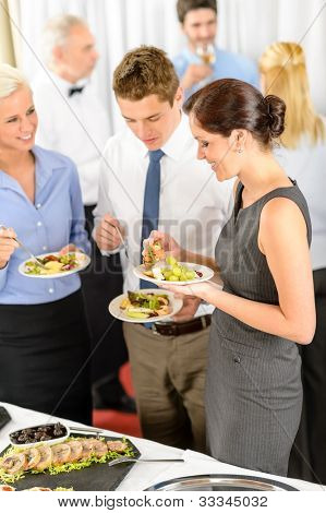 Business colleagues eat buffet appetizers catering service company event