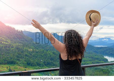 Attractive Plus Size Women Holds A Hat In Her Hands And Looks At The Mountains. Photo Taken From Beh