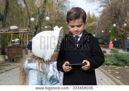 Little Girl Looks Something Interesting On Screen Of Gadget, Which Her Brother Holding In His Hands.