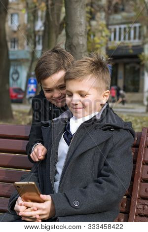 Two Boys In Business Clothes On A Bench In The Park On An Autumn Day. Children Watch Something Inter