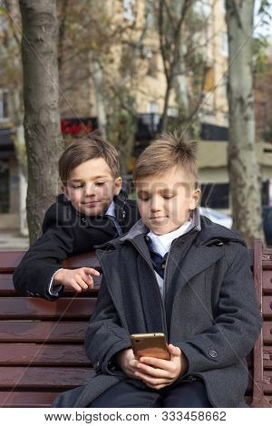 Two Schoolchildren Are Watching An Interesting Video On A Smartphone And Smiling While Sitting On A