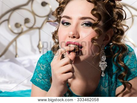 Young Happy Cheerful Curly Woman Lying In A Bed And Eating Chocolate