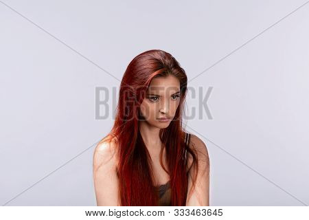 Portrait Of Young Offended Female On Light Background