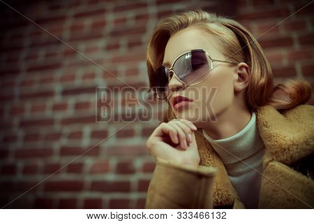 Portrait of a fashionable young woman in modern sunglasses over brick wall backgroud. Winter style. Beauty, fashion concept. Optics, eyewear.