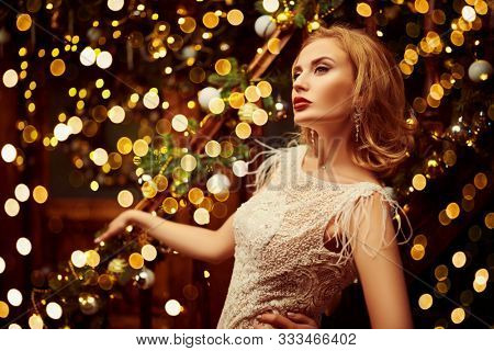 Christmas and New Year magic. Charming happy young woman in a festive evening dress and with beautiful evening makeup and hairstyle in the fairy beautiful Christmas interior. Lights around.