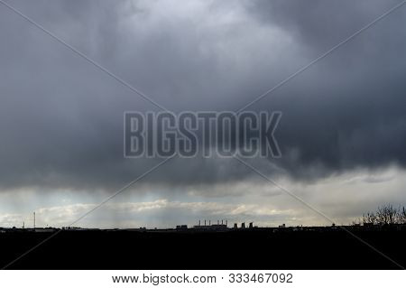 Thunderstorm Over The City On A Summer Evening. Monstrous Clouds Over Industrial Buildings On The Ho