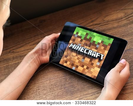 September 2019 Parma, Italy: Minecraft App Game On Tablet Screen In Kid`s Hands. Minecraft Logo Game