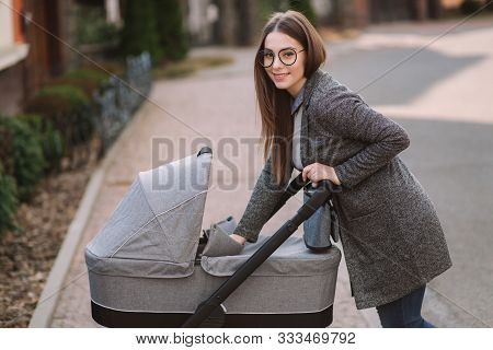 Young Mom Walking With Daughter In Stroller. Mother Cares For The Baby. Mom Look In To The Stroller