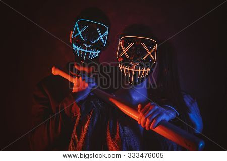 Man And Woman In Masks Are Posing For Photographer With Baseball Bat In Red And Blue Lights.