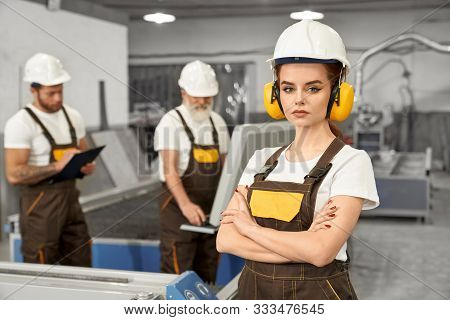 Beautiful Female Engineer Looking At Camera And Posing During Working Day On Metal Factory. Young Wo