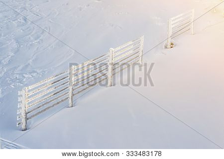 Scenic Alpine Mountain Peak With Thick Snow Layer With Icing Covered Fence Defense From Avalanche On