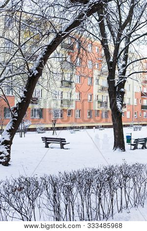 A Typical Polish Block Of Flats In Winter, With Sidewalk In Snow.