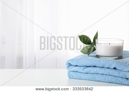 Towel, Candle And Ruscus On White Background, Copy Space. Spa
