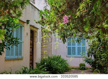 Pollenca, Mallorca, Spain, 09-16-2018: View Of Vintage House With Rich Foliage Around. Retro-styled