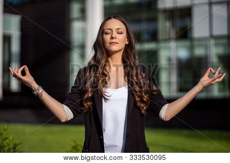 Businesswoman Is Meditating Outside The Company Building
