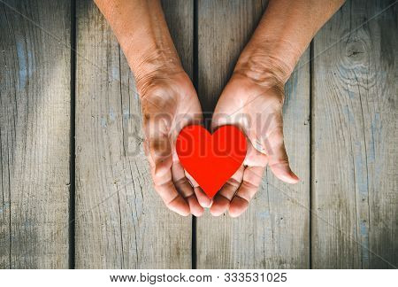 Elderly Woman Hands On Rustic Wooden Background. Senior Woman With Fingers Crossed. Wrinkled Palms S