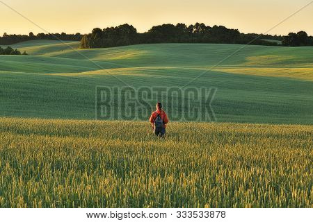 Woman In The Field. A Tourist Walks On A Hilly Field