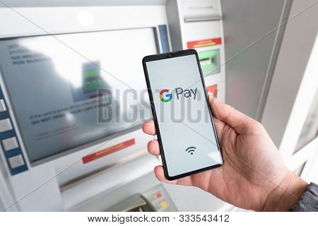 Man Holding Smartphone With Google Pay Logo
