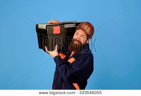 Repairman In Uniform Holds Toolbox. Manual Worker. Man With Tool Box. Builder With Box For Instrumen