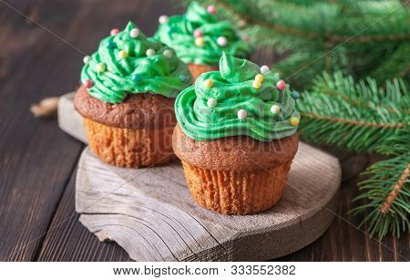 Cupcakes Decorated With Colourful Sprinkles With Christmas Tree Branch
