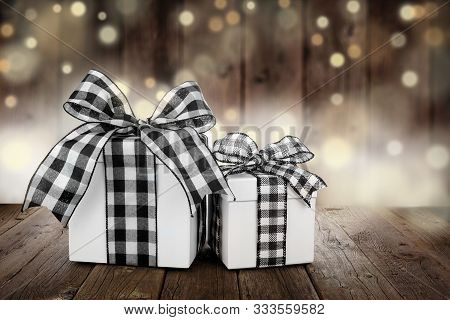 Rustic Christmas Gifts With Black And White Buffalo Plaid Check Ribbon. Side View With A Dark Wood A