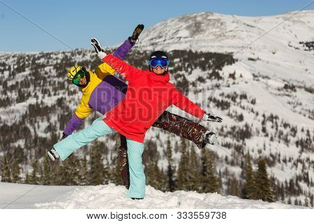 The guy and the girl snowboarders are having fun on the top of the mountain in the ski resort. Sheregesh Russia.