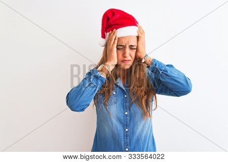 Young beautiful redhead woman wearing christmas hat over isolated background suffering from headache desperate and stressed because pain and migraine. Hands on head.