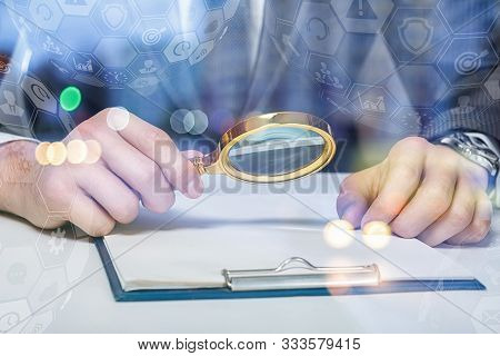 A Lawyer Or A Businessman Examining A Document With A Magnifying Glass.