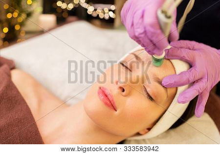 poster of people, beauty, cosmetology, exfoliation and technology concept - beautiful young woman having microdermabrasion facial treatment with crystals in spa