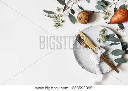 Autumn Thanksgiving Table Place Setting. Golden Cutlery, Porcelain Plate, Berry Eucalyptus Leaves An