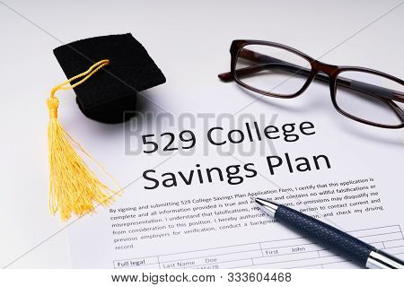 529 College Savings Plan Form With Small Graduation Hat, Spectacles And Pen Over White Background