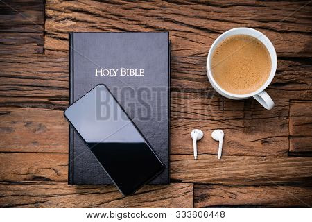 High Angle View Of Bible And A Smart Phone With Wireless Earphones And Empty Teacup