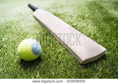 Close-up Of Wooden Cricket Bat And Ball On Turf Grass