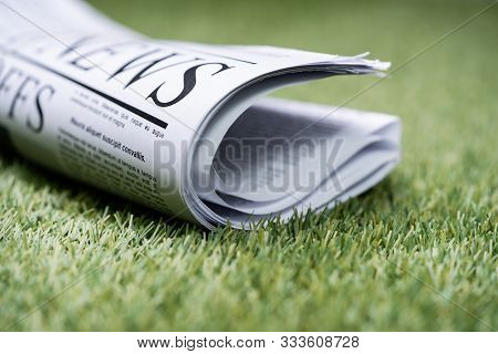 Bunch Of Newspapers Tied With Rubber Band On Green Grass At Lawn