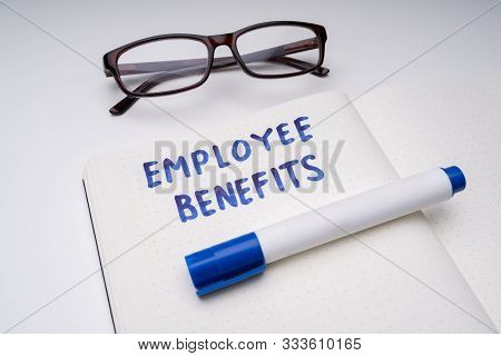 Handwritten Employee Benefits Message On Notebook With Blue Marker And Spectacles Over White Table