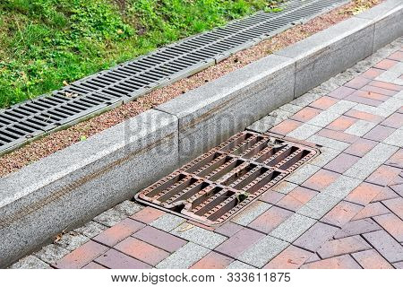 Grille Of The Drainage System Manhole On The Pedestrian Sidewalk Made Of Stone Tiles By The Curb, On
