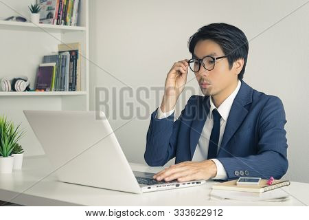 Asian Financial Advisor Or Asian Consulting Businessman In Suit Consider And Analyze Financial Data.
