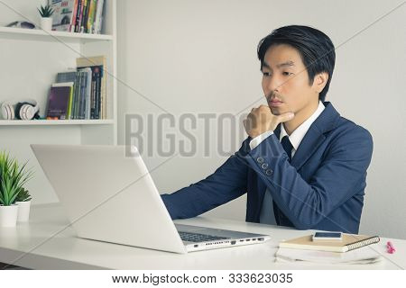 Asian Financial Advisor Or Asian Consulting Businessman In Suit Thinking In Front Of Laptop Monitor