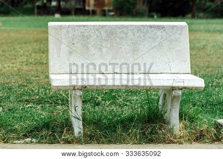 Old And Broken Long White Cement Bench For Relaxing After The Exercise Beside The Exercise Yard In T