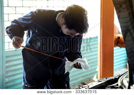 Auto Mechanic Checks The Oil In A Car Garage To Make Car Care. Concept Service By Car.