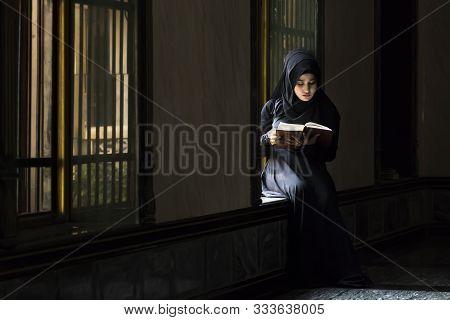 A Muslim Girl Put Black Head Scarf Was Reading Islamic Texts. Strictly