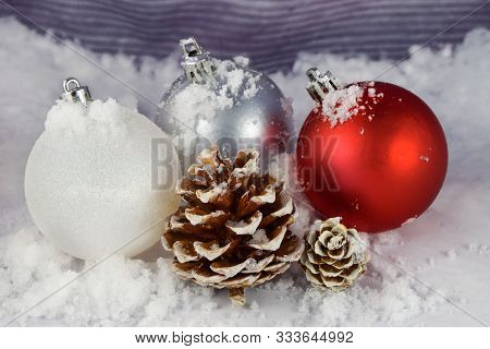 Three Christmas Ornaments And A Couple Of Pinecones Rest Atop This Wintery Background. Scattered Sno