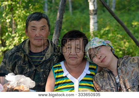 Family Portrait Of Two Elderly And One Young Daughter Yakut Asians In The Northern Forest At The Tab