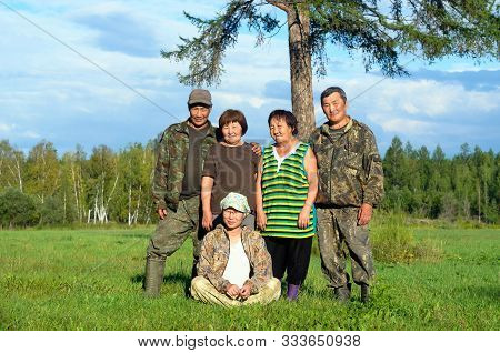 Two Yakut Asian Elderly Couples Men And Women With A Young Girl Sitting On The Grass Pose For A Fami